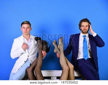 fashion and business handsome men in suit holding female legs in fashionable shoes and tights luxury and patriarchy