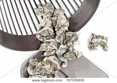 Crumpled dollars lie in a garbage scoop and partially in an inverted trash can, close-up, isolated on a white background