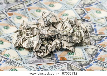 Pile of crumpled money on a background of hundred-dollar bills
