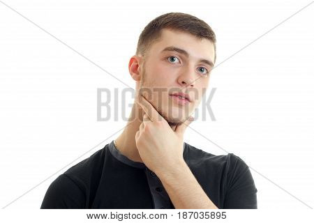 handsome young guy in the black shirt keeps hand on Chin and stares into the camera close-up isolated on white background