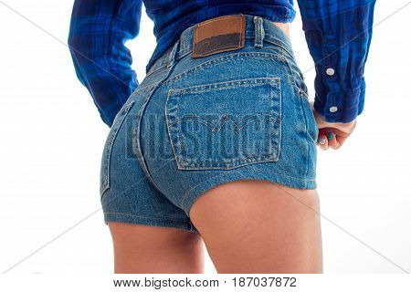 sexy buttocks of a young girl in denim short shorts close-up isolated on white background