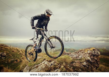 Ryder in a full-face helmet and full protective equipment on the mtb bike rides on a rock against the backdrop of the ridge and low clouds.