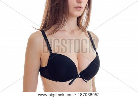 natural big sexy breasts in a black bra close-up isolated on white background