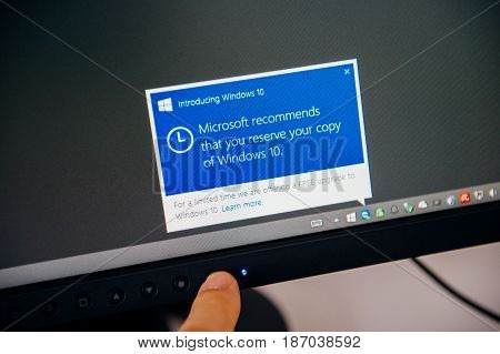 PARIS FRANCE - AUG 5 2015: Introducing Windows 10 - Man touching display with message in the dashboard Microsoft recommends to reserve the copy of Windows 10 during the free upgrade period