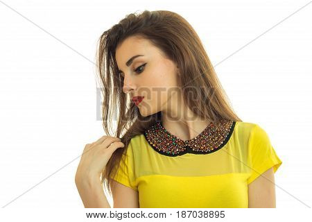 charming girl in a yellow blouse cocked her head to the side and looks down close-up isolated on white background