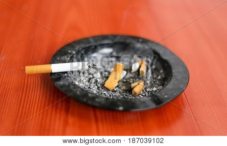 Burning cigarette in the ashtray among OFF tranquilizers with cigars harmful to health odors smoke