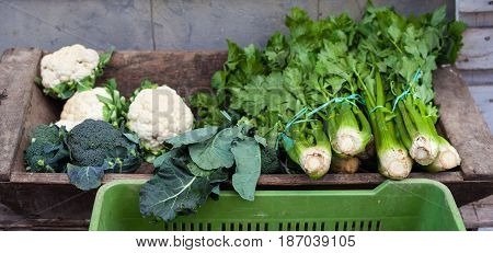 View of organic broccoli celery and cauliflower on wooden case