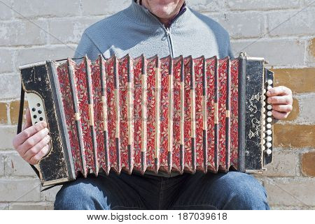 man playing with an old grunge concertina near the brick wall
