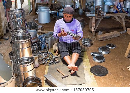 JAVA, INDONESIA - DECEMBER 21, 2016: Worker making kitchen utensils in a factory on Java Indonesia 21th december 2016.