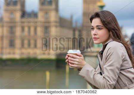 Beautiful sad, depressed or thoughtful young woman in London on Westminster Bridge over the River Thames drinking takeout coffee by Big Ben