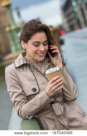 Happy, smiling, girl or young woman standing on Westminster Bridge, London, England, drinking coffee in a disposable cup and talking on a mobile cell phone