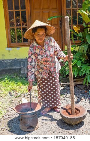 JAVA, INDONESIA - DECEMBER 21, 2016: Local woman grainding coffee beans in an old fashioned way on Java Indonesia 21th december 2016.