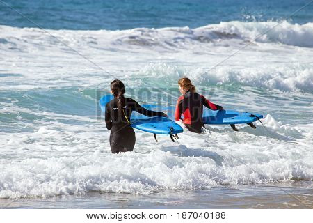 VALE FIGUEIRAS, PORTUGAL - MAY 13, 2017: Two surfers getting surfers lessons at the ocean at Vale Figueiras beach in Portugal on 13th of may 2017