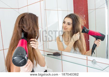smiling cute girl looks in the mirror and hair dryer dries hair closeup