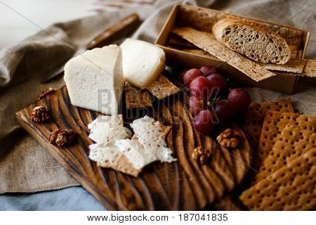Table with wine, cheese, bread, grapes and pears standing on a cozy balcony.