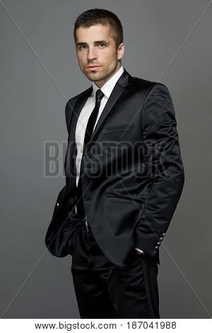 Handsome man in a black suit and tie on a gray background