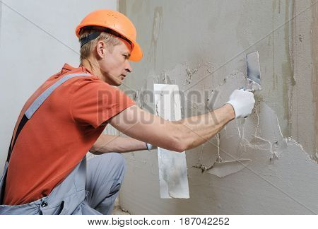 Worker is putting a gypsum plaster on a wall. He is using trowels.