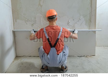 Worker is putting a gypsum plaster on a wall. He is using a long ruler.