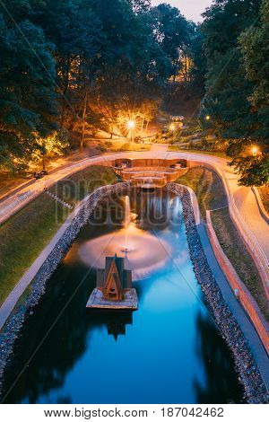 Gomel, Homiel, Belarus. Top Scenic View Of Park Watercourse Channel Flowing Into River In City Park In Evening Or Night Illumination. Lighted Walkways, Greenwood Along Watercourse At Blue Hour