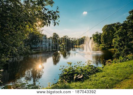 Riga, Latvia. City River Canal In The Park Bastion Hill. Sun Shining Through Green Foliage In Sunny Summer Evening. Fountains In Water Of River Canal.