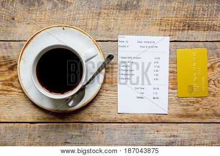 paying check for lunch in cafe with credit card on wooden table background top view