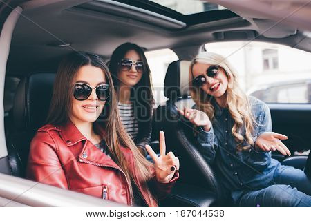 Four Beautiful Young Cheerful Women Looking At Each Other With Smile While Sitting In Car