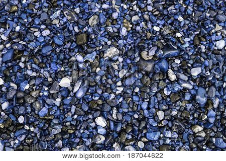 Unnatural world. Blue beach pebbles. Stones and gravel used as decorative driveway aggregate. Background texture and pattern image representative of environmental manipulation and chemical pollution.