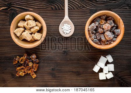 lumps of sugar in bowls on wooden kitchen table background top view