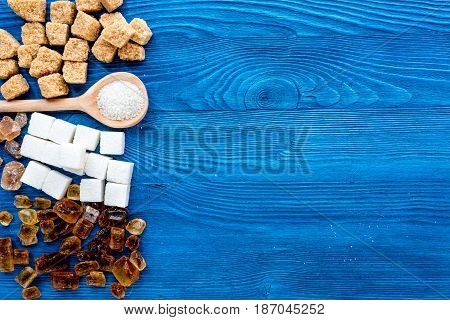 lumps and sanding sugar for cooking sweets on blue kitchen table background top view mock up