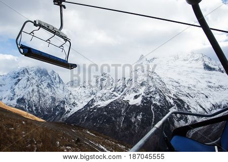 view on cable car at ski resort and mountains in sunlight clouds. Caucasus Mountains, region Dombay