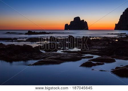 Pan di Zucchero Island which looks like a cube of sugar during sunset near Porto Flavia on the coast of Sardinia, Italy, Europe. There is also very nice area for climbing.