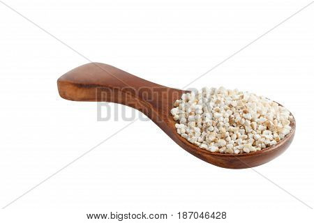 Barley groats on wooden spoon isolated on white background.