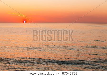Sun Is Setting On Horizon At Sunset Sunrise Over Sea Or Ocean. Tranquil Sea Ocean Waves. Natural Sky Warm Colors. Panoramic View, Panorama. Copy Space.