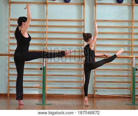 Rhythmic gymnastic teacher and little girl lessons.