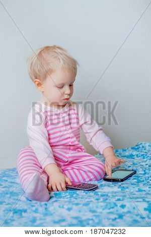 Cute adorable white Caucasian blond baby making a call playing with mobile cell phone with funny expression on face lifestyle new generation technology early development