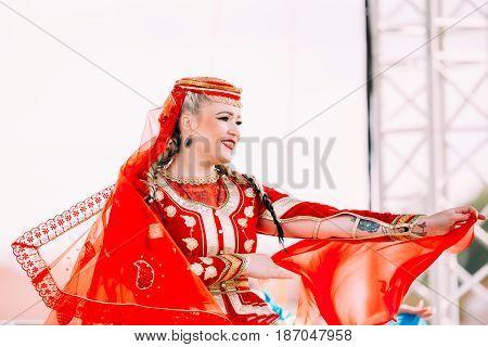 Minsk, Belarus - September 3, 2016: Young woman dressed in traditional folk costume dancing Azerbaijani folk dances.