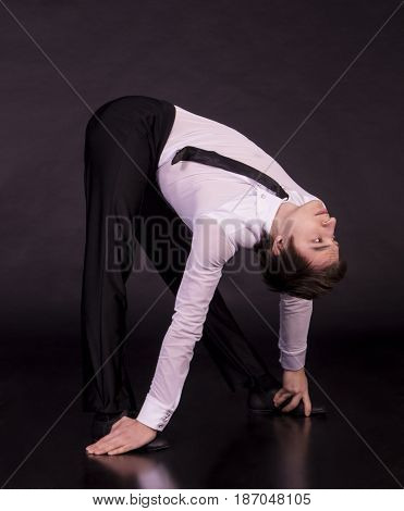 Extraordinary gymnast on a black background. The man with no bones. Studio photography of circus performers.