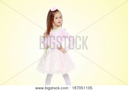 Dressy little girl long blonde hair, beautiful pink dress and a rose in her hair.She keeps hands on hips.On a yellow gradient background.