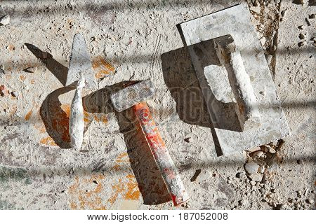 Mason tools on debris background in house improvement construction