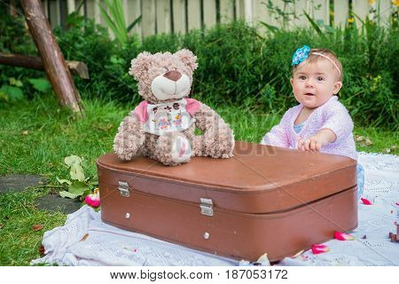 Baby sitting near suitcase in the summer garden