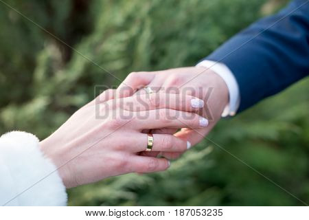 Love and marriage. Wedding ceremony. bride dresses gold ring on finger of groom