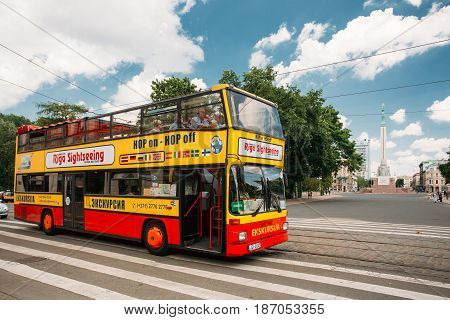 Riga, Latvia - July 2, 2016: Touristic Bus For Sightseeing In Kalku Street With View Of Freedom Monument On Background.  City Sightseeing Tour.