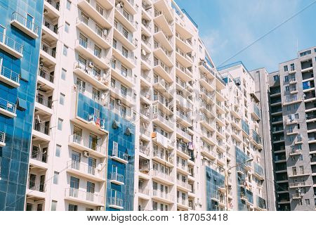 Wall With A Balcony Of New Modern Multi-storey Residential Building House In Residential Area On Sunny Blue Sky Background