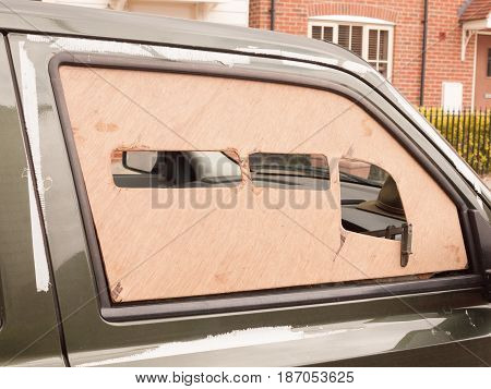 A Car Window Boarded Up With Wood Panel Outside