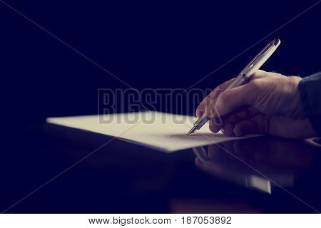 Businessman signing a document or taking notes close up view of his hand and the paper retro effect faded look.