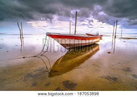 Fishing boat against colorful sky with clouds and low tide beach at sunset in Labuan island,Malaysia.Nature background.