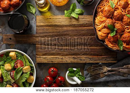 Spaghetti with tomato sauce and meatballs, fresh vegetable salad and red wine overhead shot with copy space