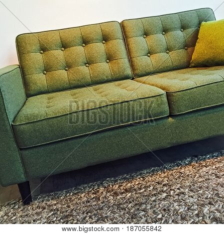 Retro style elegant green sofa on a knitted wool rug.