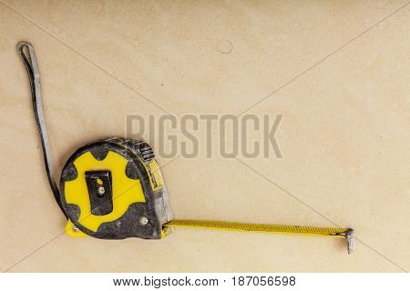 Crafting tinkering objects. Black and yellow measuring tape lying on brown floor.