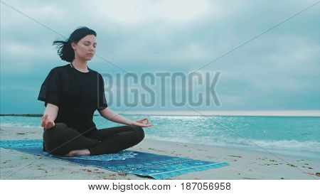 Fitness woman in sports clothing practicing yoga on the sea ocean beach close up to water. Dolly shot. Calm young woman sitting in lotus pose.